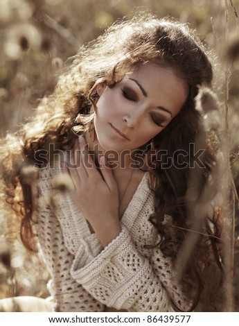 autumn woman closeup portrait with nature on the background