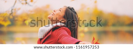 Autumn woman happy smiling feeling free in fall nature. foliage yellow colors of nature. Asian girl by the lake panoramic banner landscape.