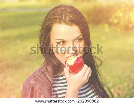 Autumn woman happy smiling outdoors, beautiful Woman holding autumn apples and fruits. Portrait of young woman walking outdoors at fall. Attractive woman walking in autumn park.