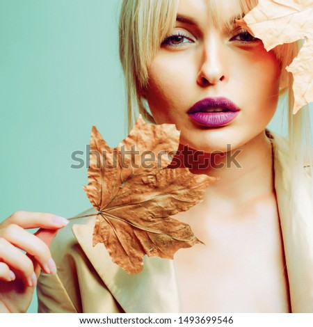 Autumn woman. Hello September. Model face close-up. Autumnal foliage. Autumn Clothing. Autumn leaves background. Autumn Clothing and color trends