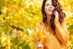 Autumn woman in autumn park. Warm sunny weather. Fall concept