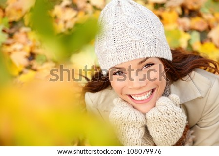 Autumn woman in yellow leaves portrait. utumn portrait of happy lovely and beautiful mixed race Asian Caucasian young woman in forest in fall colors.