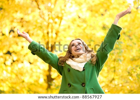Autumn woman standing with arms raised