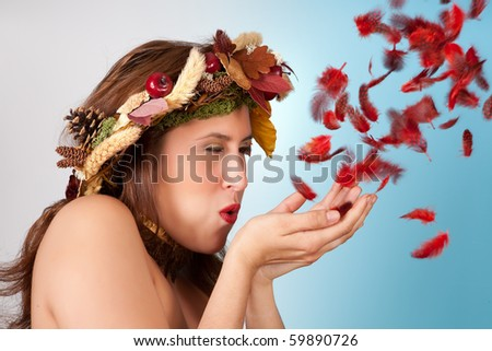 Autumn woman with garland of leaves in her hair blowing red feathers