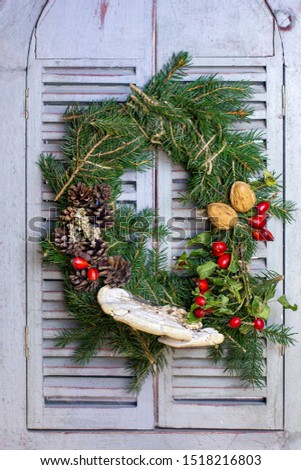 Autumn wreath from pine needles, pine cones, rosehips nuts and tree mushrooms. Coming fall DIY. Ornament on a wooden window. #1518216803