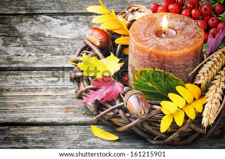 Autumn wreath with candle on wooden background