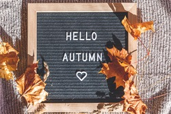 Autumnal Background. Black letter board with text phrase Hello Autumn and dried leaves lying on white knitted sweater. Top view flat lay. Thanksgiving banner. Hygge mood cold weather concept