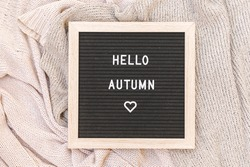 Autumnal Background. Black letter board with text phrase Hello Autumn lying on white knitted sweater. Top view flat lay. Thanksgiving banner. Hygge mood cold weather concept