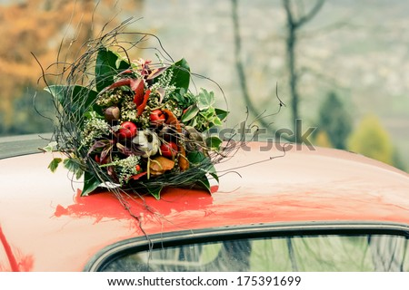 Autumnal bouquet on the top of retro car. The noise is added for art purposes #175391699