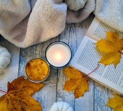 Autumnal composition on blue wooden surface with lighted candle, open book, blanket, white faux pumpkins and yellow maple leaves. Top view, from above, flat lay. Relaxing at home and hygge concept.