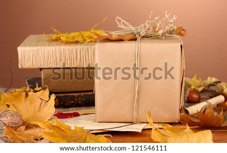Autumnal composition with gift, books and leaves on brown background