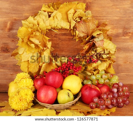 Autumnal composition with yellow leaves, apples and mushrooms on wooden background - stock photo