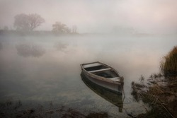 Autumnal foggy landscape. A beautiful view at the river with a lonely old wooden boat parked on the stony beach.