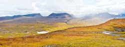 Autumnal mountain landscape of Abisko National Park in northern Sweden with lapporten valley in background.