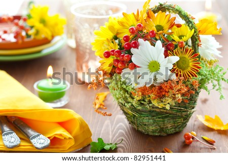 autumnal place setting with basket of autumn flowers