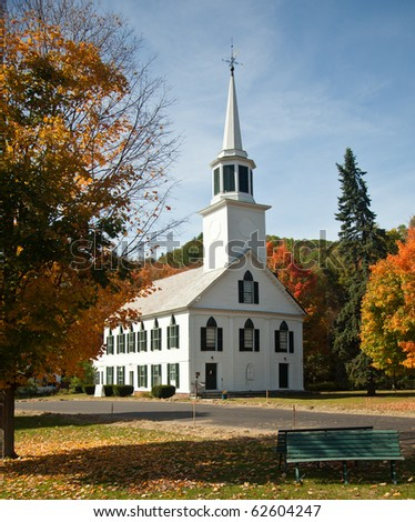 Autumnal shot of the typical Vermont church in fall as the bright trees turn orange and red