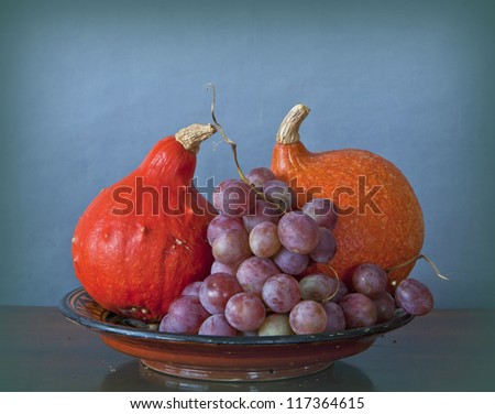 Autumnal still life: tray with red pumpkins and purple grapes on a wooden table and on blue background