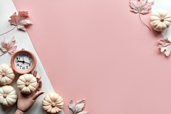 Autumntime background. Alarm clock in wooden model hand, and decorative white pumpkins. Layered off white and orange paper flat lay with dry maple leaves. Seasonal arrangement, monochromatic look.