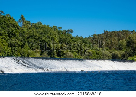 Ave River in Portugal, fast flowing water gushing over weir with trees on horizon. Foto stock ©