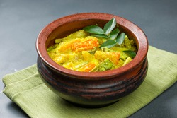 Avial_Kerala traditional  side dish,  made using mixed vegetables and it is very healthy and tasty dish ,arranged in an earthenware with grey coloured background