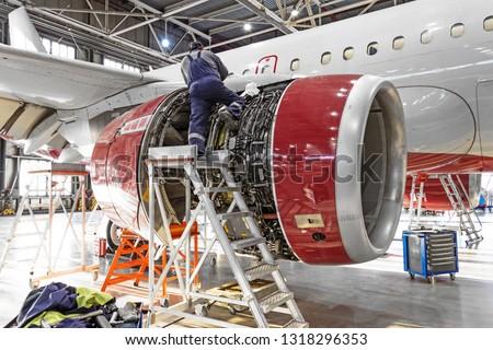 Aviation industry, mechanic repairs aircraft engine jet.