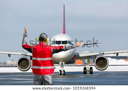 Aviation Marshall / Supervisor meets passenger airplane at the airport. Ground Crew in the signal vest.