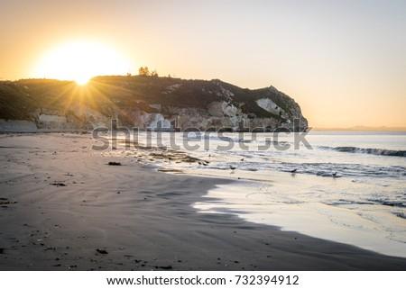 Avila Beach sunrise behind the cliff on the ocean