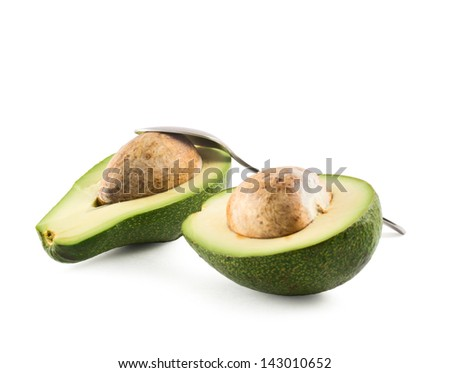 Avocado alligator pear fruit sliced in two halves composition with a metal spoon isolated over white background