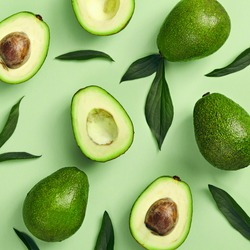 Avocado and green leaves pattern on green background. Top View. Pop Art design, creative summer food concept. Green avocadoes, eco and healthy food minimal flat lay. Banner organic food minimal