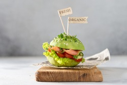 Avocado burger with salted salmon and fresh vegetables, sesame seeds and microgreen. Healthy raw food, keto dieting recipe. Organic food. Side view, copy space for text. Restaurant menu
