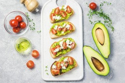 Avocado cherry tomatoes feta cheese toasts on board. Top view, space for text.