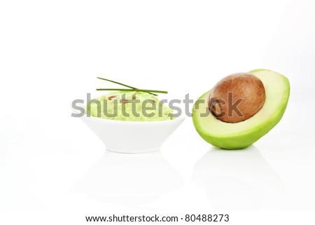 Avocado dip guacamole and fresh avocado half isolated on white background.
