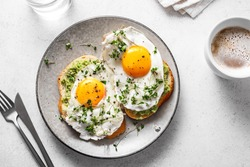 Avocado Egg Sandwiches and coffee for healthy breakfast. Whole grain toasts with mashed avocado, fried eggs and organic microgreens on white table.