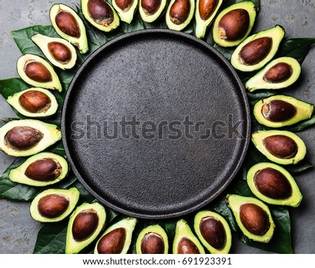 Avocado. Frame made from avocado palta and avocado tree leaves around black plate. Guacamole ingredients. Healthy fat, omega 3. Half of avocado. Top view. Copy space #691923391