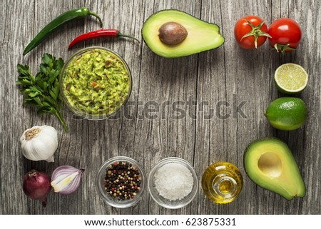Avocado guacamole with fresh ingredients on wooden table Foto stock ©