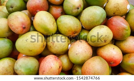 Avocado Mangoes on a market stand, ripe for eating. There are many different mango varieties but they all require tropical climates to survive. This particular variety was grown in Mexico.