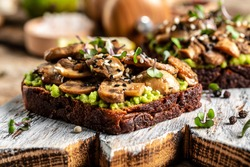 avocado, mushrooms and microgreen whole grain sandwich. Decorated with sesame. Vegetarian food. Vegan menu. Food recipe background. Close up.