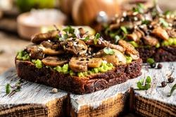 avocado, mushrooms and microgreen whole grain sandwich. Decorated with sesame. Vegetarian food. Vegan menu. Food recipe background. Close up.