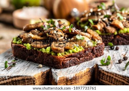 avocado, mushrooms and microgreen whole grain sandwich. Decorated with sesame. Vegetarian food. Vegan menu. Food recipe background. Close up. Stock photo ©