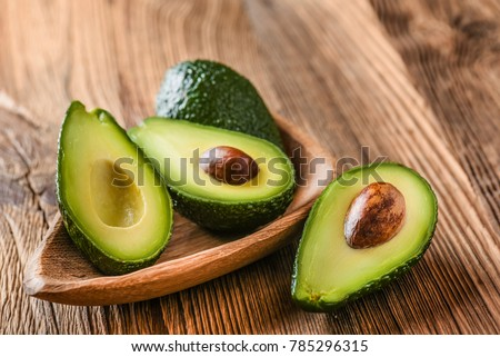 Avocado on old wooden table.Halfs on wooden bowl. Fruits healthy food concept.