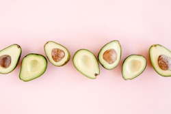Avocado on pink background. Tropical abstract background with avocado. Food concept. flat lay, top view