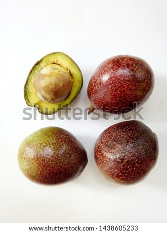 Avocado on white background, some avocado species in Chiang Mai,have an oval fruit with relatively large seed, thin flesh and creaminess,when riped has reddish-brown peel,light yellow meat.Thailand.