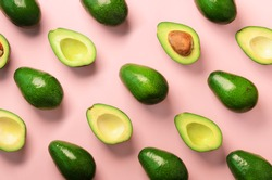 Avocado pattern on pink background. Top view. Banner. Pop art design, creative summer food concept. Green avocadoes, minimal flat lay style