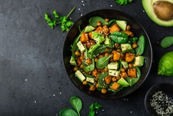 Avocado, quinoa, roasted sweet potato, spinach and chickpeas salad in black bowl. Top view, copy space