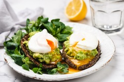 Avocado rye bread toast with poached egg on plate. Healthy appetizer, breakfast, lunch or snack. Runny egg yolk