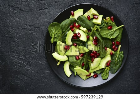 Avocado salad with baby spinach and pomegranate on a black plate on a slate,stone or concrete background.Top view with copy space.
