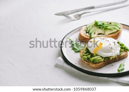 Avocado Sandwich with Poached Egg - sliced avocado and egg on toasted bread for healthy breakfast or snack, copy space.