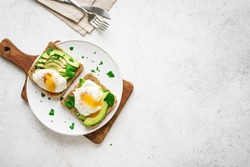 Avocado Sandwiches with Poached Eggs - sliced avocado and egg on toasted bread for healthy breakfast or snack, copy space.