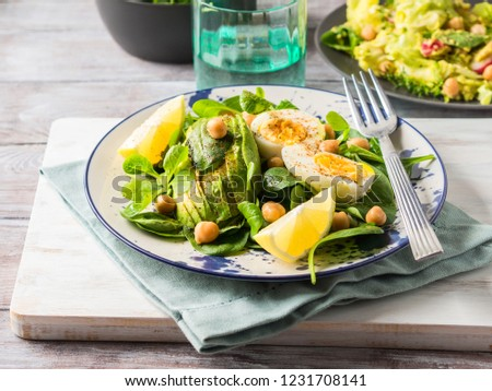 Avocado spinach salad with chickpeas and hard boiled eggs served on a dish. Fats and proteins #1231708141