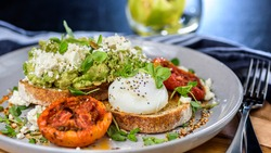 Avocado Toast featuring smashed avocado, grilled tomatoes, boiled egg on sourdough toast